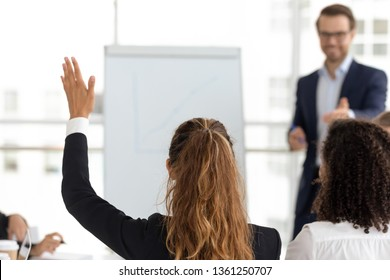 Training participant raise hand ask question get engaged involved in voting initiative at employees team workshop, corporate knowledge, business education, volunteer participation concept, rear view