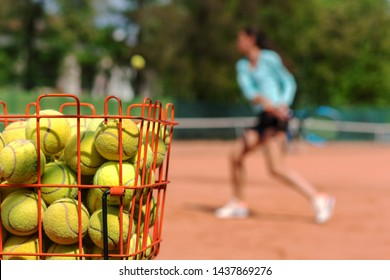 training process on game of tennis on clay courts in tennis academy, young athlete strikes backhand with racket on ball, foreground basket with tennis balls