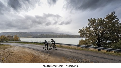 Training in a rainy day in autumn season. Pair of cyclists.