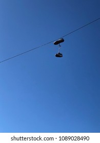 Training shoes hanging from overhead cable