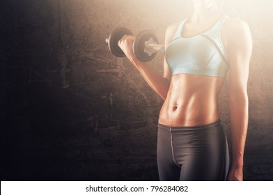 Training woman with dumbbells in her hand