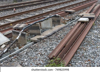 trainstation with train passing by and rails with infrastructure beside in south germany city near munich and stuttgart