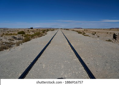 Traintracks leading to the horizont into nowhwere at the train cemetery close to Uyuni in the Altiplano of Bolivia, South America