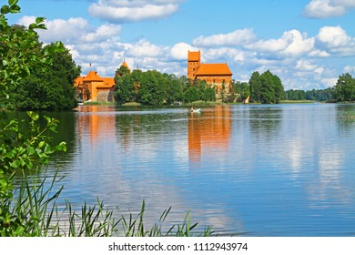 Trakai Historical National Park, UNESCO world heritage site, on summer day. Trakai Island Castle, a major tourist attraction, reflecting in clear water of Galve lake. Couple on catamaran swimming.