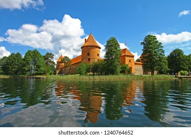 Trakai Historical National Park, UNESCO world heritage site, on beautiful summer day. Trakai Island Castle, major tourist medieval attraction, reflecting in clear water of Galve lake. White clouds