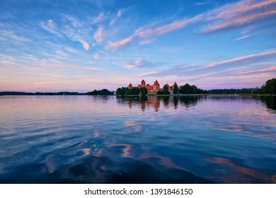 Trakai Island Castle in lake Galve, Lithuania on sunset with dramatic sky reflecting in water. Trakai Castle is one of major tourist attractions of Lituania