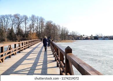 Trakai, Lithuania - April 04, 2018: Road in the park near Island castle in Trakai and touristd on it. One of the most popular touristic destinations in Lithuania in early spring