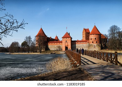 Trakai, Lithuania - April 04, 2018: Island castle in Trakai and tourist near it. One of the most popular touristic destinations in Lithuania in early spring