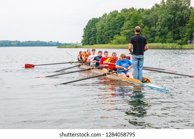 Trakai, Lithuania - July 26, 2013: Instructor coach teaching a tourists how the eight rowing boat works in the waters of Galve lake. Eight is a rowing boat used in the sport of competitive rowing.