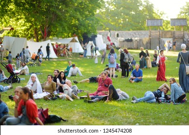 TRAKAI, LITHUANIA - JUNE 16, 2018: Kids and adults enjoying historical reenactment on annual Medieval Festival, held in Trakai Peninsular Castle. Visitors watching the jousting show.