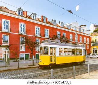 Tram 28, the famous yellow tram in Lisbon on a sunny day, with a red building on background. Summer postcard from Portugal, toned image. Travel and architecture concepts