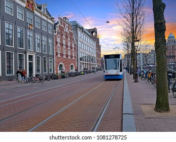 Tram driving in the city center from Amsterdam in the Netherlands at sunset
