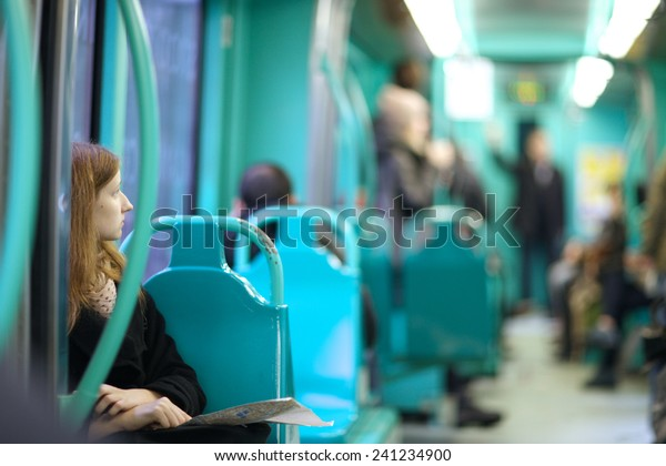 Tram interior, young woman looking aside to other passengers