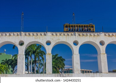 Tram of Santa Tereza (Bonde de Santa Teresa) drives along distinctive white arches (Arcos da Lapa) of the landmark in historic district of Rio de Janeiro - Brazil.