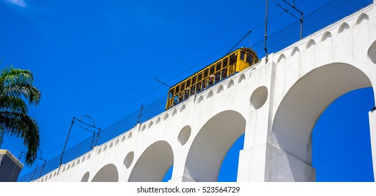Tram of Santa Tereza (Bonde de Santa Teresa) drives along distinctive white arches (Arcos da Lapa) of the landmark in historic district of Rio de Janeiro - Brazil.