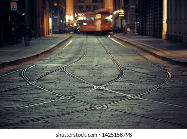 Tram track in street in Milan, Italy at night.