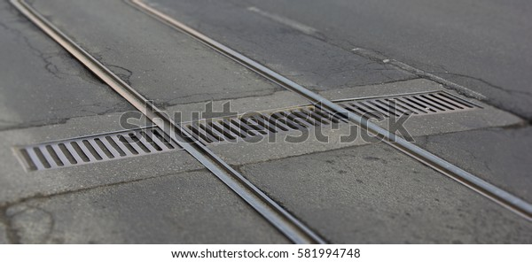 Tram tracks in the street intersect the drainage cover.