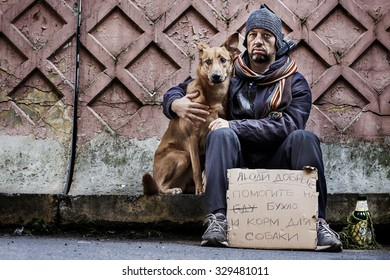 """A tramp and his dog with sad faces are cadging with a plate. On the plate is written on russian language """"Please give me some money for alcohol and dog food"""" . Image with toning and selective focus"""