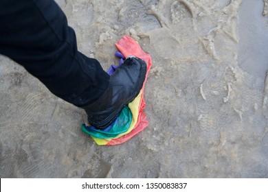 Trampling of LGBT flag in dirt by radical homophobe.