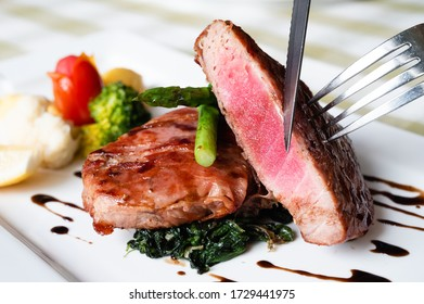 Trancio Di Tonno, tuna steak wrapped with bacon with spinach, asparagus, lemon, tomato, potato and broccoli. Eating with knife and fork.