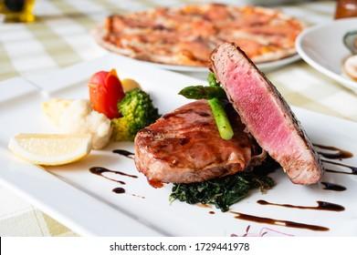 Trancio Di Tonno, tuna steak wrapped with bacon with spinach, asparagus, lemon, tomato, potato and broccoli.