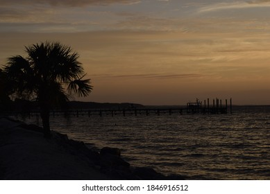 Tranquil beach scene with glowing sky and fading sunset over a calm sea and silhouette of palm trees and pier on the horizon
