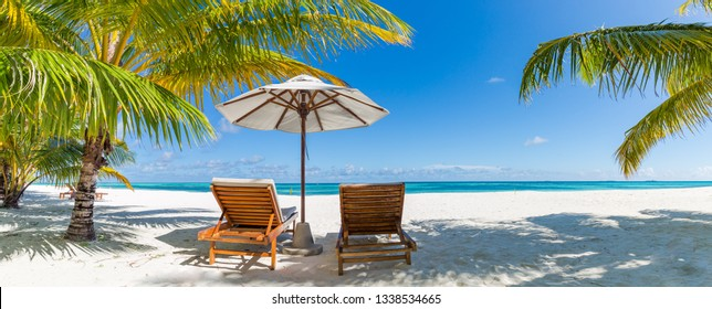 Tranquil beach scene. Panoramic tropical beach landscape for background or wallpaper, two lounge chairs with umbrella. Design of summer vacation holiday concept