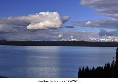 Tranquil, calm Lake Pukaki mirrors tufts of white clouds New Zealand