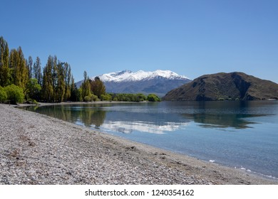 Tranquil clear water with reflections of snowy mountains in Lake Wanaka, Wanaka, South Island, New Zealand.