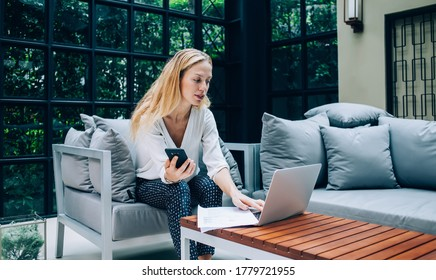 Tranquil female executive manager in elegant outfit typing on netbook while sitting with cellphone in armchair and working remotely in cafe