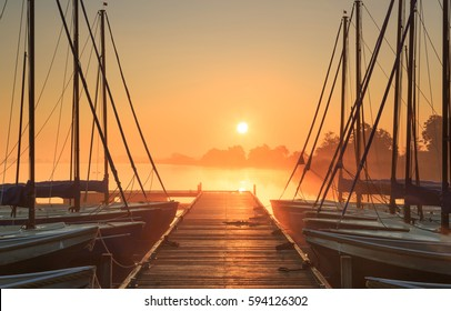 Tranquil and foggy sunrise at a small marina with sailing boats.