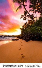 Tranquil Footprints in the Sand with Beautiful Colorful Sky at Sunset and Calm Ocean Water Coming on Sandy Beach Shore with Palm Trees Silhouette and Lush Greenery on Big Beach in Maui Hawaii