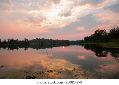 Tranquil lake and golden cloudy sky in sunset time