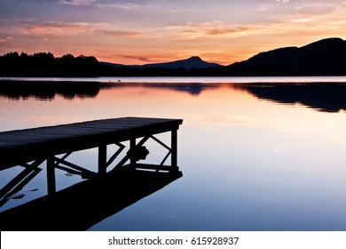Tranquil lake with jetty at sunset and conical shaped mountain in the distance. Lake of Menteith, Loch Lomond and The Trossachs National Park, Scotland, UK