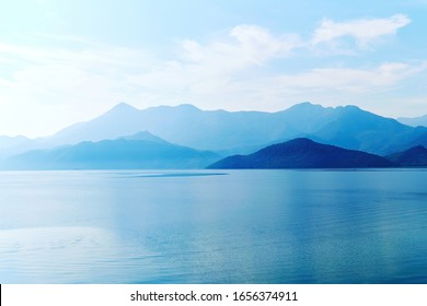 Tranquil landscape of mountains and lake water in the sunrise lights. Morning fog over the water surface. Skadar lake, Montenegro. Nature background - Shutterstock ID 1656374911