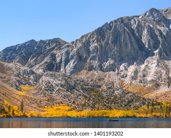Tranquil landscape with a small fishing boat sailing on the beautiful Convict Lake on a sunny autumn day in the Eastern Sierra mountains. Bright yellow trees reflecting on the water surface.