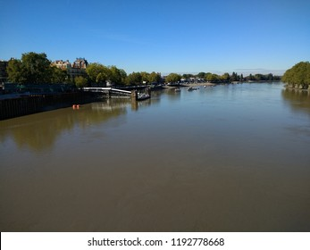 Tranquil Landscape view over the River Thames at Putney in London England viewed from the bridge looking out across the wide still calm waters with trees and buildings and blue sky on warm Autumn day