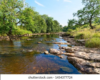 A tranquil late afternoon in summer beside the River Ribble as it flows through Stainforth.