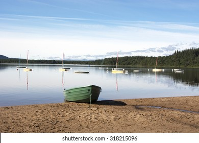 Tranquil Loch with Boats: a green boat partially hauled up onto a sandy beach, infront of a group of sailing boats floating on a very calm loch.  Loch Morlich, Cairngorm National Park Scotland