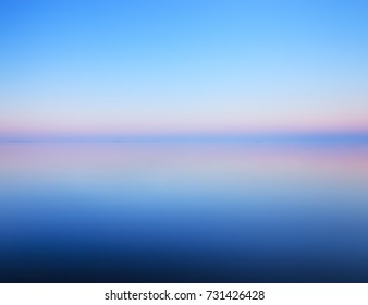 Tranquil minimalist landscape with smooth surface of the lake with calm water with horizon with clear blue sky in twilight, simple beautiful calm natural blue background