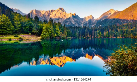 Tranquil morning scene of Fusine lake. Captivating summer sunrise in Julian Alps with Mangart peak on background, Province of Udine, Italy, Europe. Beauty of nature concept background.