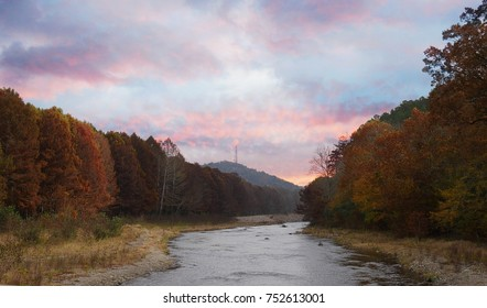 The tranquil Mountain Fork River flowing at the Beavers Bend State Park in Broken Bow, Oklahoma with colorful leaves on the trees on a beautiful autumn day.