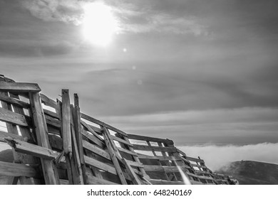 A tranquil mountain scene with clouds cover and fence on a hill. Black and white.