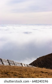 A tranquil mountain scene with clouds cover and fence on a hill. Pastel colors sky in the background.