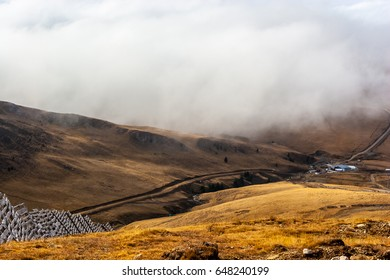 A tranquil mountain scene with clouds cover and fence on a hill. Some cabins in the backgroud.