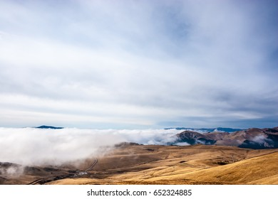 A tranquil mountain scene with clouds cover on a hill. Some cabins in the backgroud.