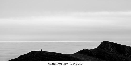 A tranquil mountain scene with clouds cover on a hill. Black and white.