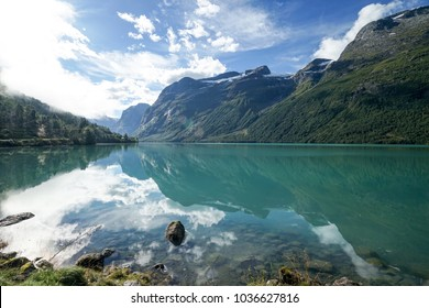 Tranquil reflection of great nature on a surface of green water in Loen, Norway. Transparent river, fjord.