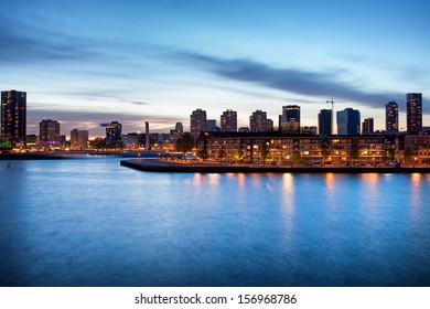 Tranquil river view of the Rotterdam city centre in Holland, Netherlands at dusk.