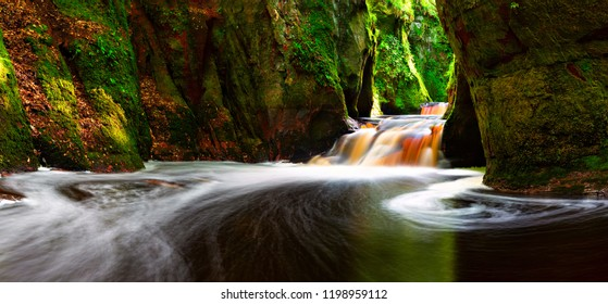 Tranquil scene of flowing water in the Finnich Glen aka Devil's Pulpit near Loch Lomond, Scotland.